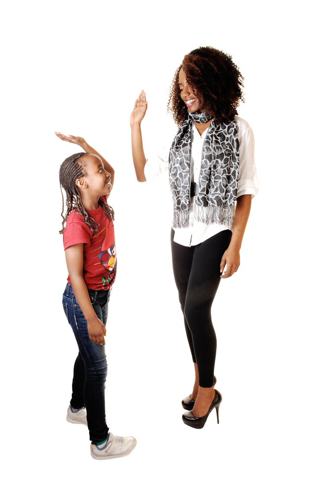 Mother and daughter with each other for white background in the studio, in jeans and tights.