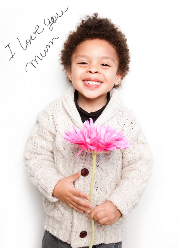 Child with big smile and big pink flower with I love mum message .