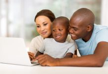 adorable young african american family using laptop at home
